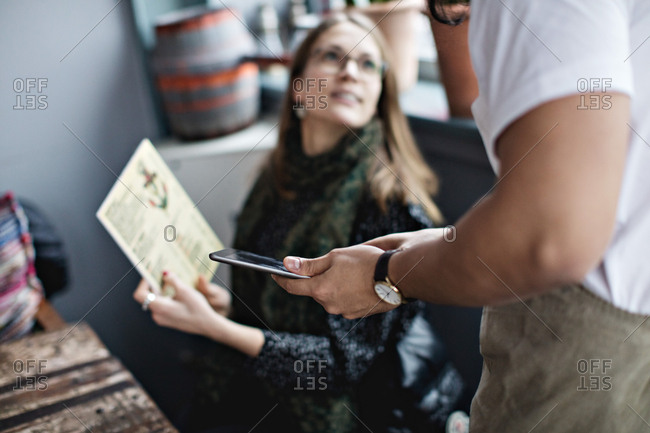 Female customer asking from menu to waiter holding digital tablet at restaurant