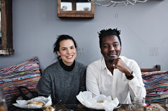Portrait of smiling multi-ethnic friends sitting at dining table in restaurant