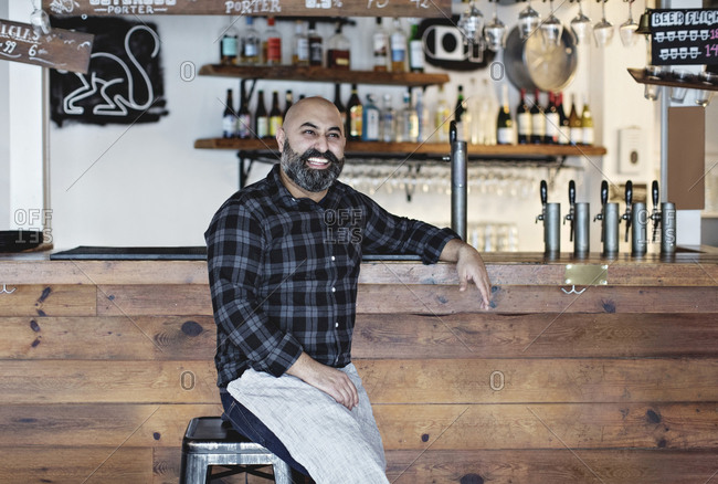 Confident smiling bartender sitting by bar counter