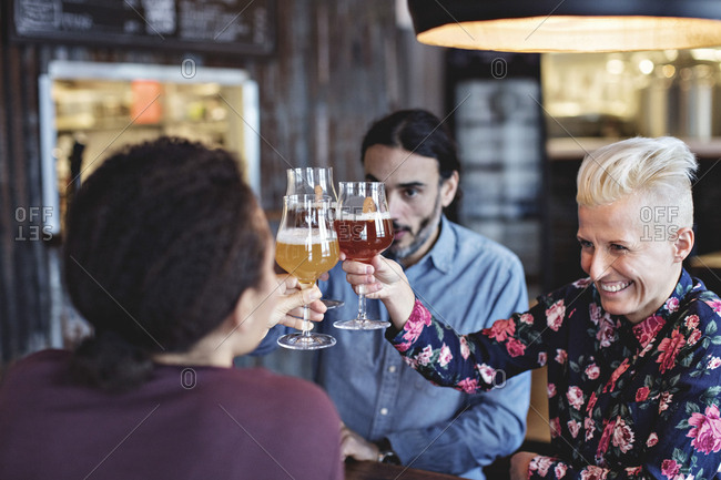 Multi-ethnic friends toasting glasses while sitting at bar