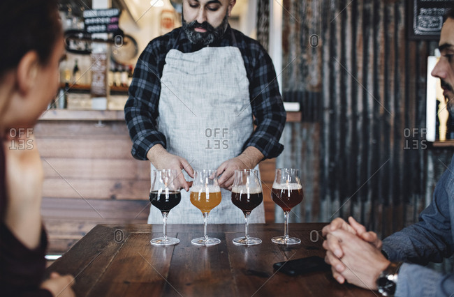 Bartender explaining about various craft beer to customers at bar