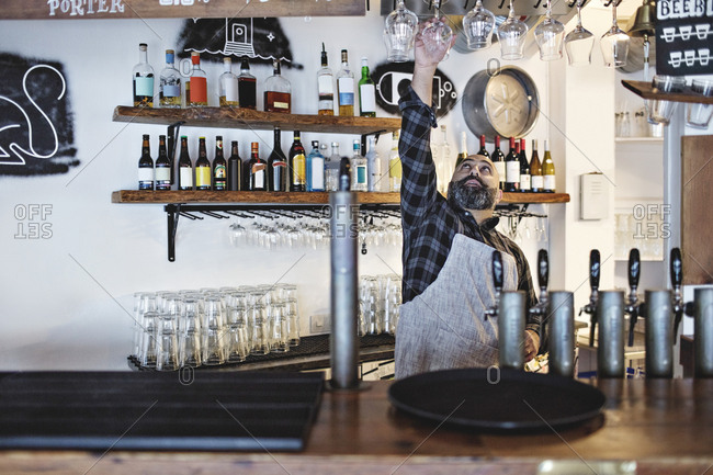 Bartender arranging wineglasses while standing at bar counter