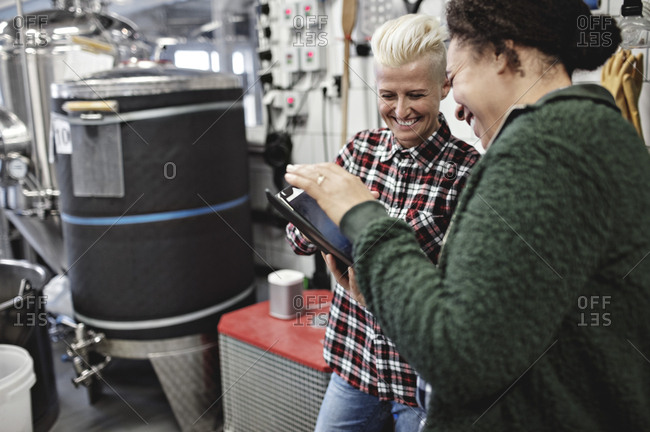 Smiling female workers discussing over digital tablet while working in brewery