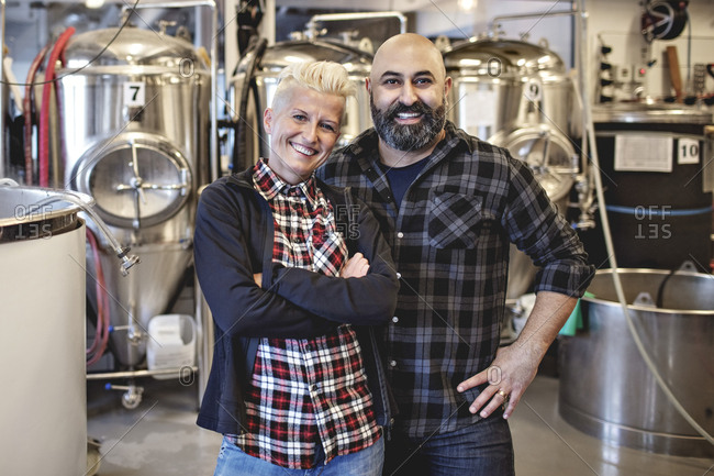 Portrait of smiling male and female partners standing in brewery