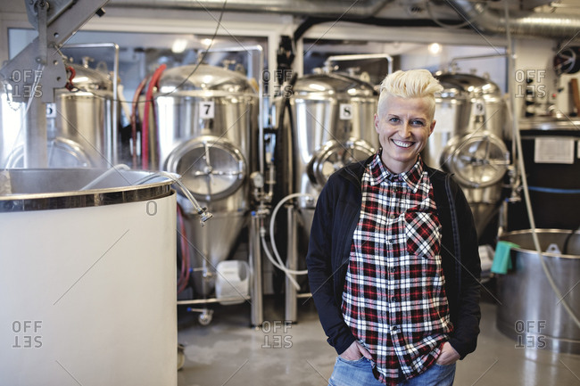 Portrait of smiling female manager standing with hands in pockets at brewery