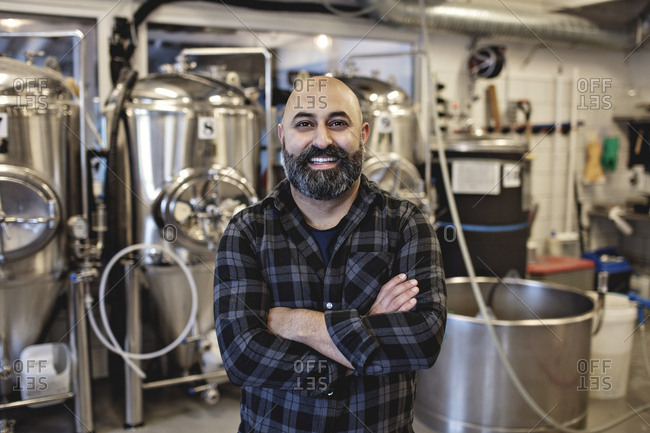 Portrait of smiling manager standing with arms crossed at brewery