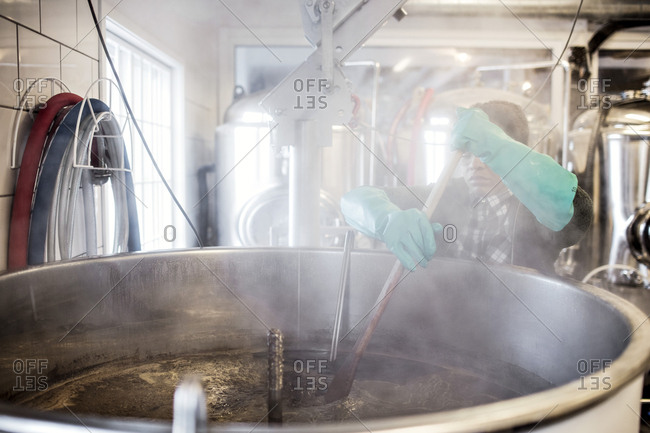 Worker wearing glove while stirring beer in container at brewery