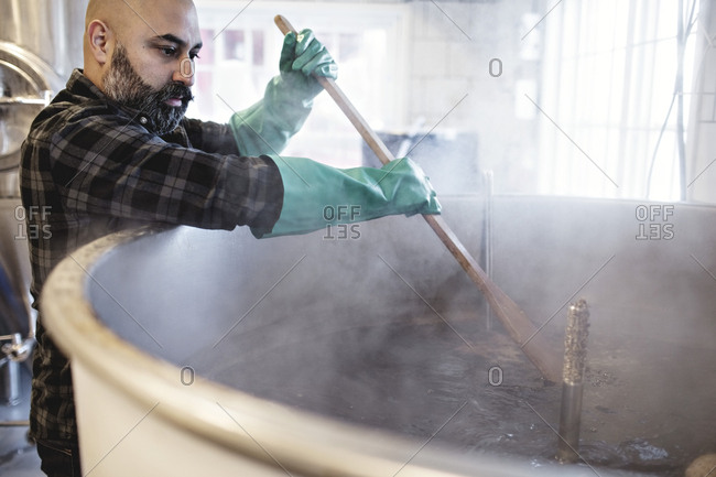 Mid adult worker stirring beer in container while working at brewery