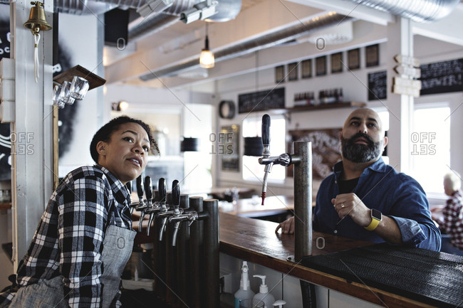 Female bartender with male customer looking up while standing at bar counter