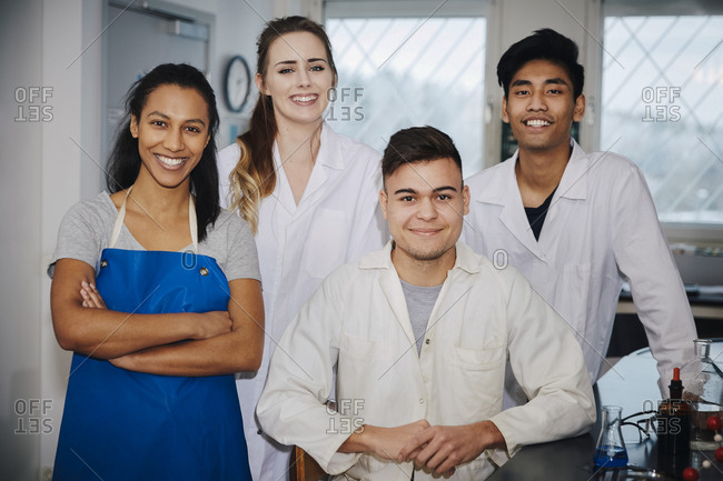 Portrait of confident young multi-ethnic engineering students in chemistry laboratory at university