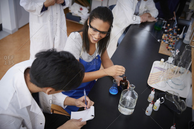 High angle view of smiling multi-ethnic students mixing solutions and writing in spiral notepad at chemistry laboratory