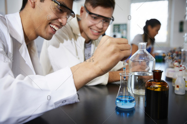 Smiling young male students mixing solutions in glassware at chemistry laboratory