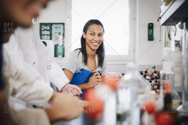 Confident female student looking at friends sitting in chemistry laboratory