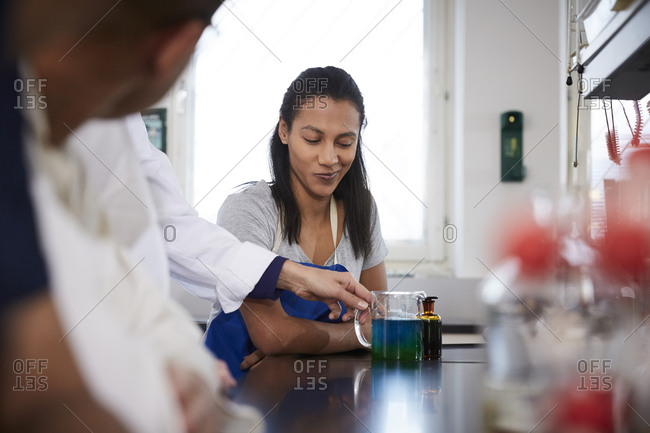 Female student looking at teacher holding beaker with solution in chemistry laboratory