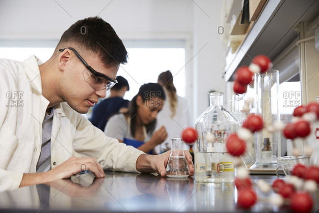 Confident young male chemistry student by friends in laboratory at university