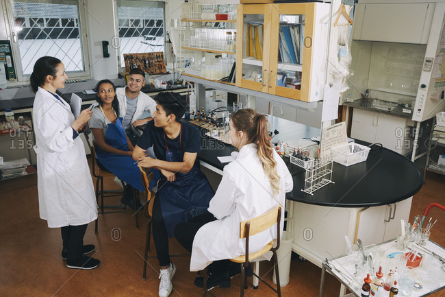 Full length of mature teacher explaining to young multi-ethnic university students sitting in chemistry laboratory
