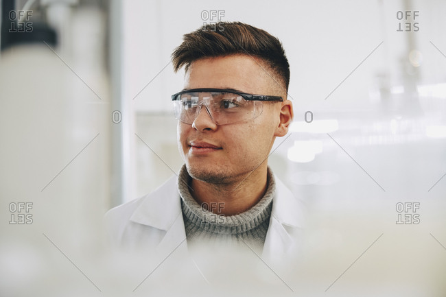 Confident young chemistry student wearing eyewear looking away in laboratory