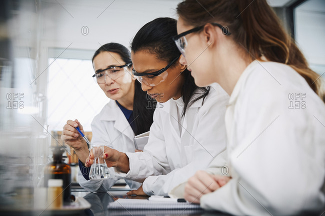 Female chemistry teacher explaining to young multi-ethnic students in laboratory