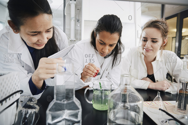 Mature chemistry teacher looking at young university student mixing liquid solution in beaker