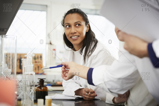 Cropped mature female chemistry teacher explaining to young students in laboratory