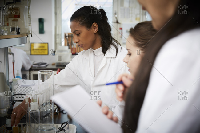 Female students with teacher studying in chemistry laboratory