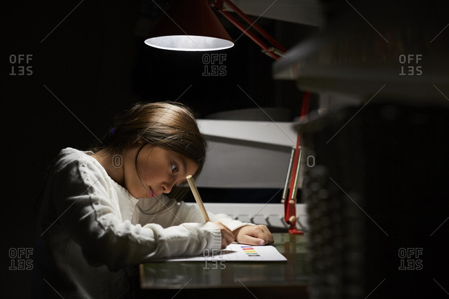 Girl studying while sitting at illuminated desk in darkroom