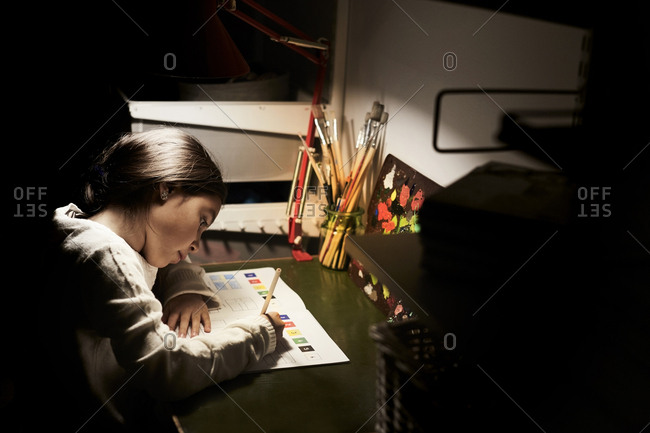 High angle view of girl studying while sitting at illuminated desk in darkroom