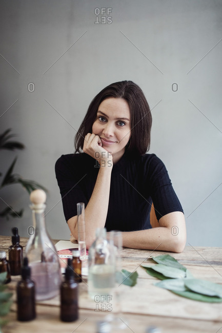 Portrait of confident female owner sitting with hand on chin at table against wall in perfume workshop