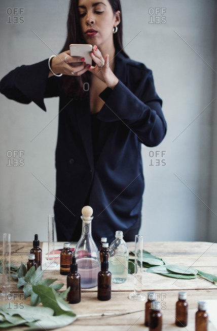 Mid adult female entrepreneur photographing perfume bottles with smart phone on table against wall at workshop