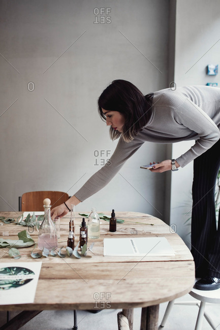 Full length of young woman standing on chair arranging table at perfume workshop