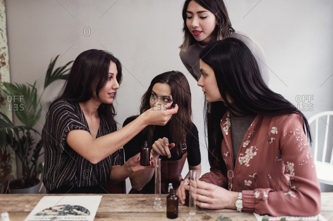 Young woman showing perfume pipette to female colleagues at workshop
