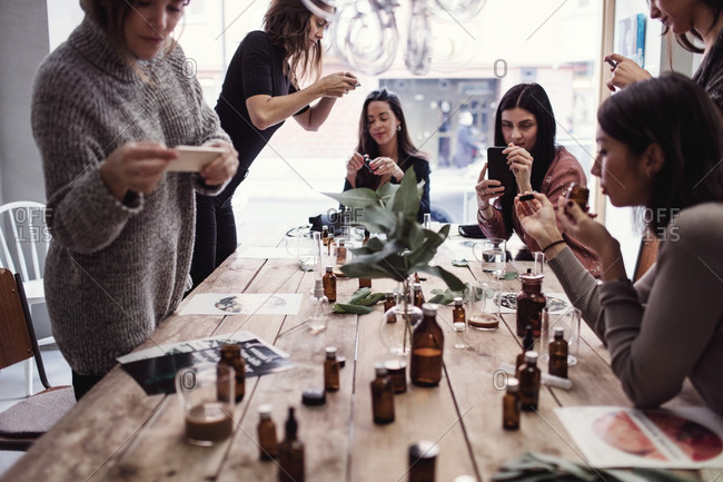 Multi-ethnic female coworkers photographing perfumes on table at workshop