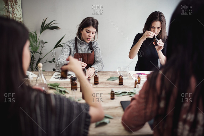 Multi-ethnic female colleagues preparing perfume while sitting at table in workshop
