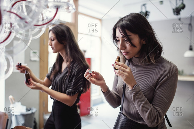 Young multi-ethnic female colleagues smelling perfume bottle while standing at workshop