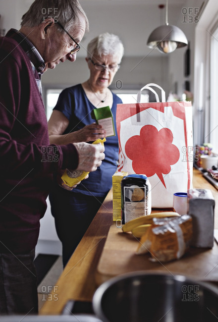 Retired senior couple with groceries on kitchen counter at home