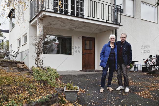 Full length portrait of retired senior couple standing against house