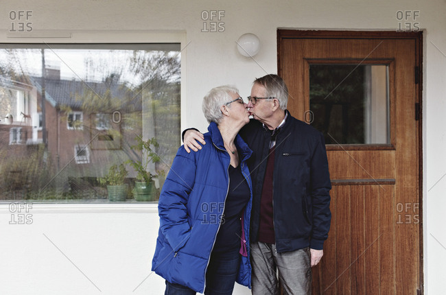 Retired senior couple kissing while standing against house