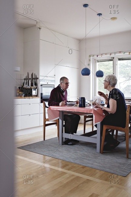 Full length of senior couple eating food at dining table
