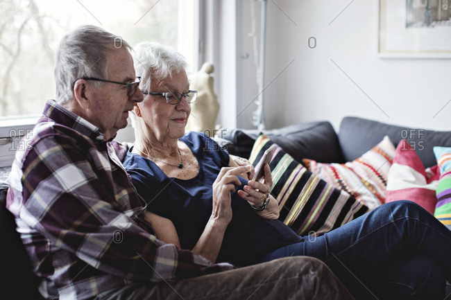 Retired senior couple sharing smart phone sitting on sofa in living room at home