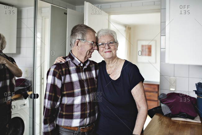 Portrait of smiling senior woman standing with man in bathroom at home