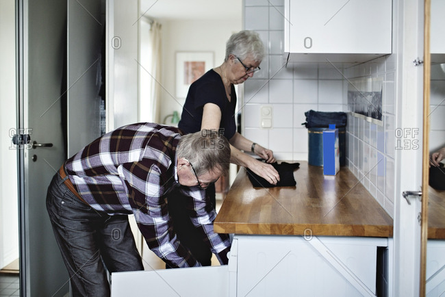 Side view of retired senior couple working in bathroom at home
