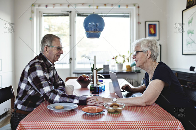 Side view of senior couple holding hands while sitting at dining table
