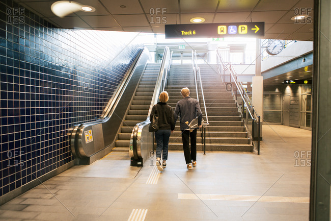 Full length rear view of young couple walking towards staircase at subway station