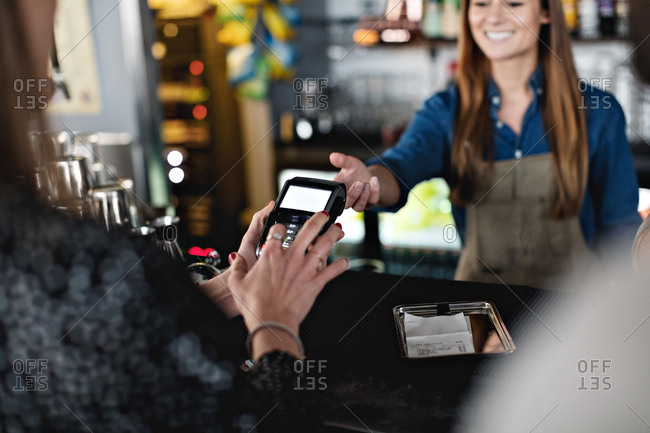 Female customer doing contactless payment to smiling owner at checkout counter
