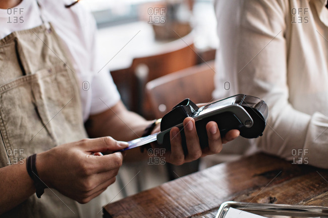 Owner using credit card reader while standing by male customer at table