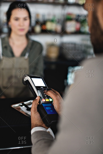 Customer using credit card reader to pay female waiter at checkout counter