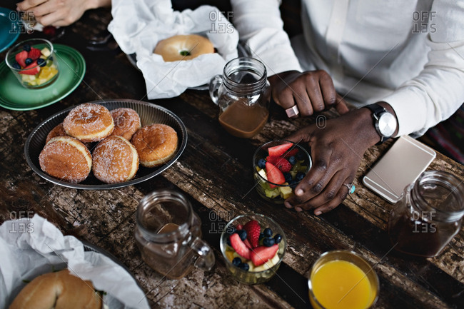 Midsection of young man having brunch at dining table