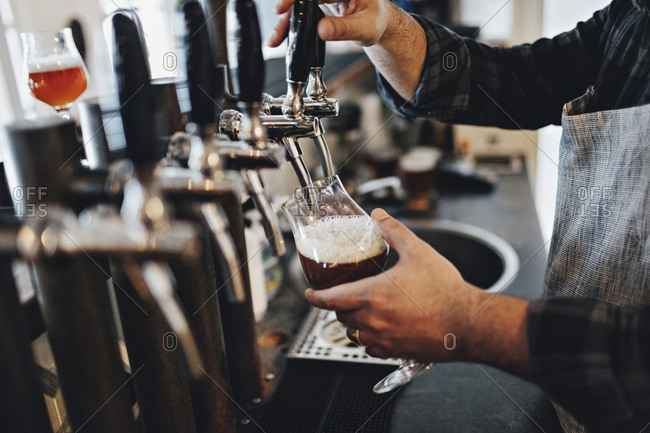 Midsection of bartender filling glass while using beer tap at restaurant