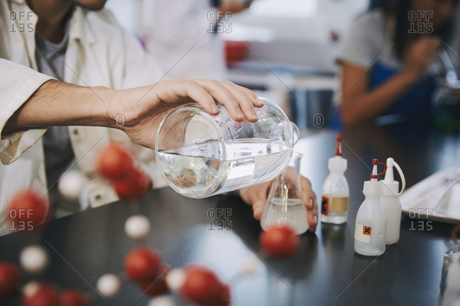 Midsection of young male student pouring liquid solution in flask on table at laboratory