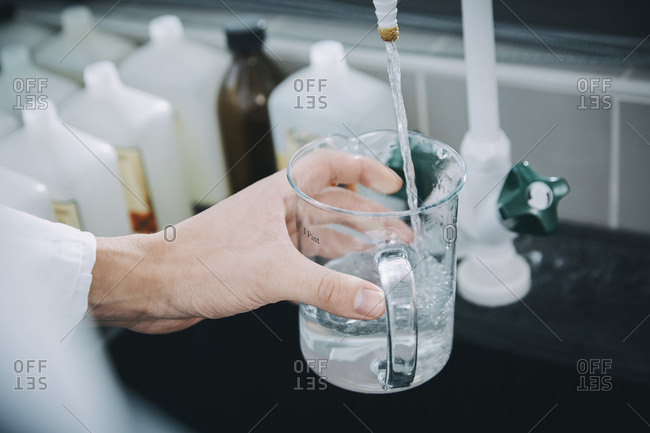 Cropped hand of female student filling beaker with liquid solution in chemistry laboratory